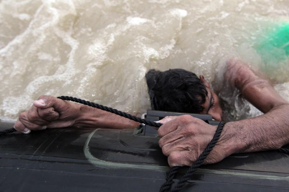 14. PAKISTAN, Sukkur, 10 sierpnia 2010: Mohammed Nawaz wyłowiony z wody, resztą sił trzyma się pontonu ratowników. (Foto: Paula Bronstein/Getty Images)