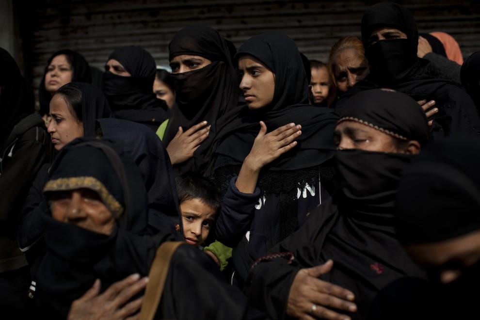 15. INDIE, New Delhi, 17 grudnia 2010: Kobiety i dzieci przyglądają się przechodzącej procesji. (Foto: Daniel Berehulak/Getty Images)