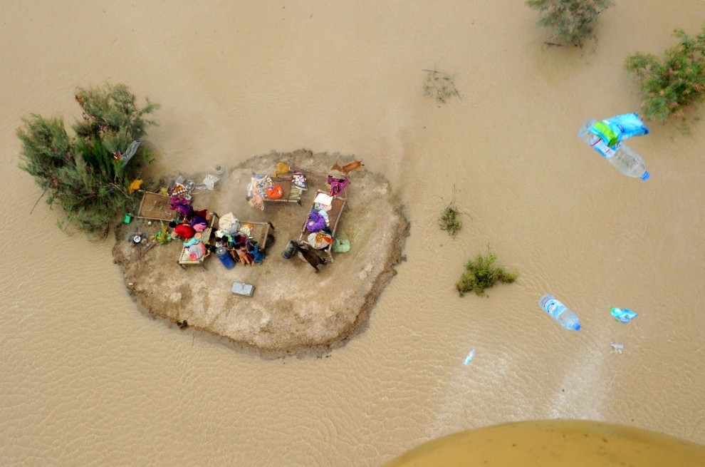 15. PAKISTAN, Ghazi Gaht, 9 sierpnia 2010: Ludzie wraz z całym dobytkiem chronią się na powstałej wysepce. AFP PHOTO/ARIF ALI