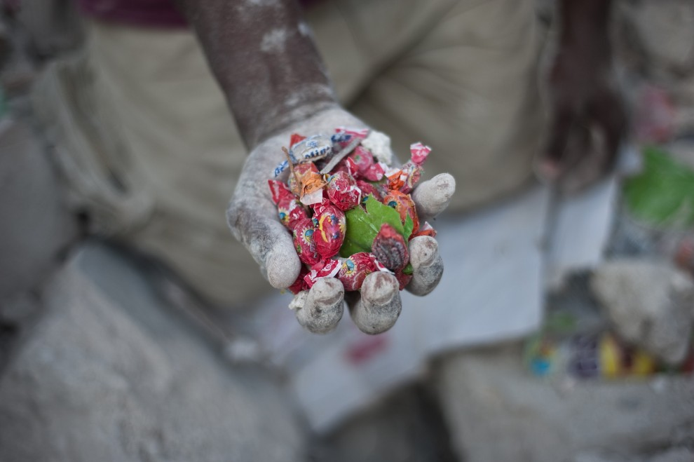 16. HAITI, Port-au-Prince, 27 stycznia 2010: Chłopiec pokazuje słodycze, ktore znalazł w gruzach budynków. AFP PHOTO / FRED DUFOUR