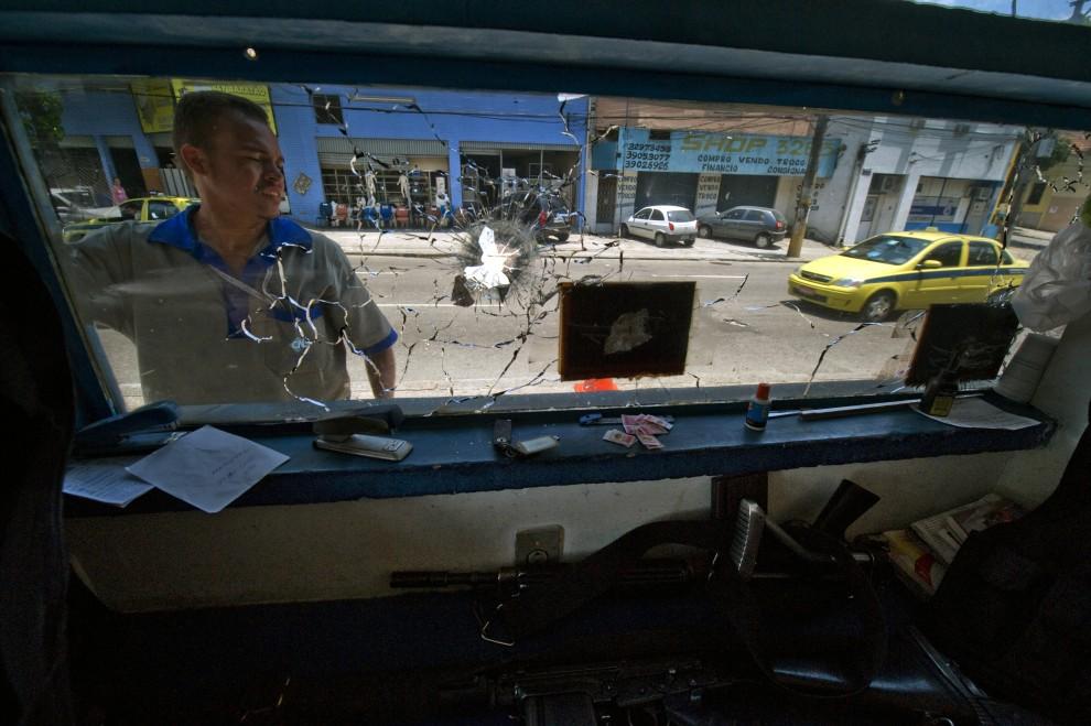 16. BRAZYLIA, Rio de Janeiro, 23 listopada 2010: Mężczyzna wymienia szyby w ostrzelanym posterunku policji. AFP PHOTO/Antonio Scorza