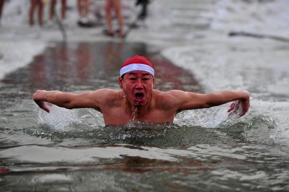17. CHINY, Shenyang, 20 grudnia 2010: Mężczyzna pływa w lodowatej wodzie rzeki Shen. AFP PHOTO