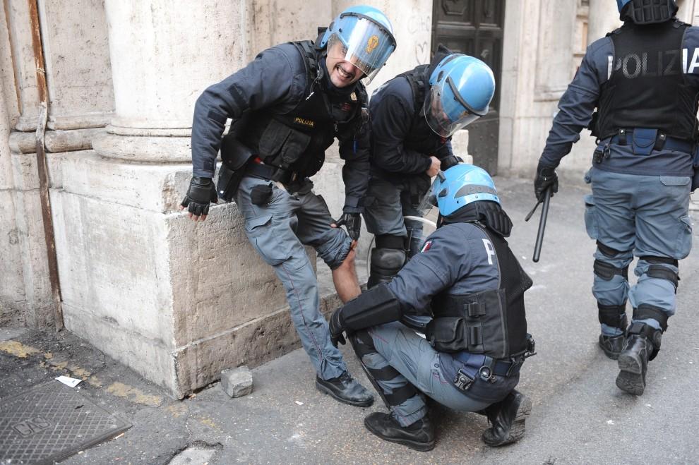 18. WŁOCHY, Rzym, 14 grudnia 2010: Ranny policjant opatrywany przez kolegów. AFP PHOTO / VINCENZO PINTO