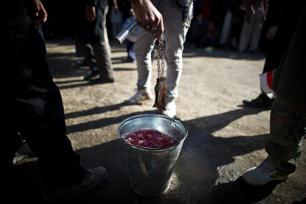 18. AFGANISTAN, Kabul, 16 grudnia 2010: Mężczyzna obmywa ostrza noży w wiadrze. AFP PHOTO / MARTIN BUREAU