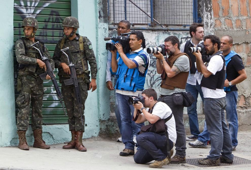 18. BRAZYLIA, Rio de Janeiro, 27 listopada 2010: Dziennikarze w towarzystwie żołnierzy pracują przy wejściu do faweli  Morro de Alemao. AFP PHOTO/Jefferson BERNARDES