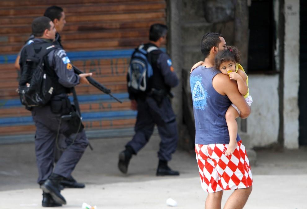 19. BRAZYLIA, Rio de Janeiro, 28 listopada 2010: Mężczyzna z dzieckiem przechodzi w pobliżu oddziału policji. AFP PHOTO/Jefferson BERNARDES