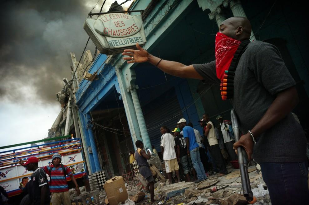 19. HAITI, Port-au-Prince, 19 stycznia 2010: Uzbrojony pracownik prywatnej firmy ochrony pilnuje dostępu do zniszczonego budynku. AFP PHOTO / OLIVIER LABAN-MATTEI