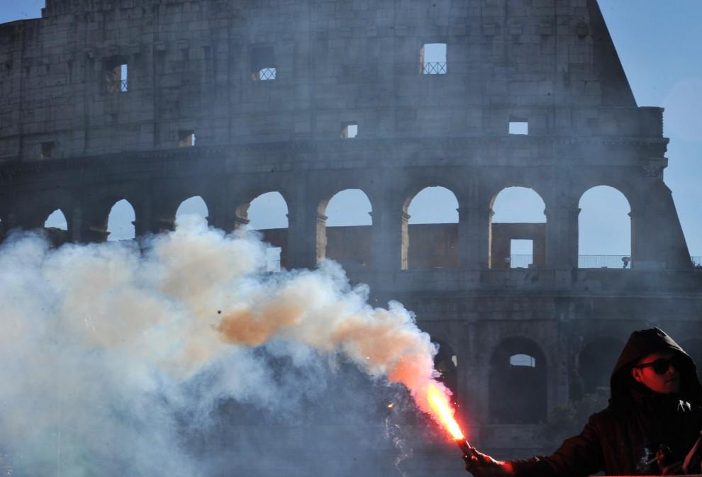 1. WŁOCHY, Rzym, 14 grudnia 2010: Protestujący trzyma płonącą racę na tle Koloseum. AFP PHOTO / ALBERTO PIZZOLI