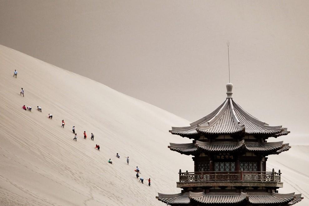 1. CHINY, Jiuquan, 20 lipca 2010: Turyści wspinają się na śpiewające wydmy pustyni w prowincji Gansu. (Foto: Feng Li/Getty Images)