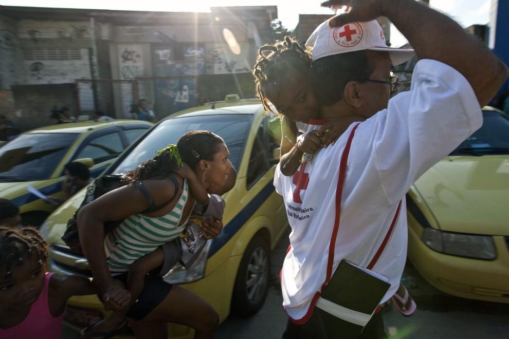 20. BRAZYLIA, Rio de Janeiro, 27 listopada 2010: Pracownik Czerwonego Krzyża pomaga przy ewakuacji mieszkańców Morro do Alemao. AFP PHOTO/ Jefferson BERNARDES