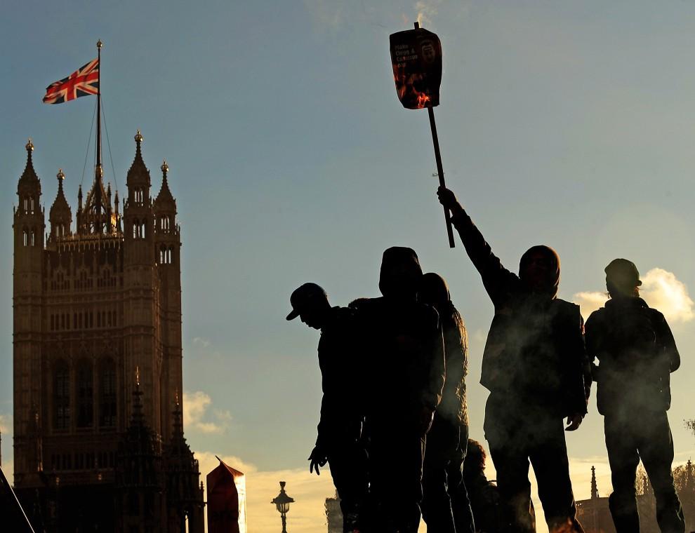 21. WIELKA BRYTANIA, Londyn, 9 grudnia 2010: Protestująca w Londynie młodzież na tle budynku parlamentu. AFP PHOTO/CARL DE SOUZA