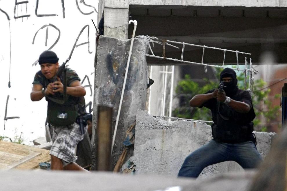 22. BRAZYLIA, Rio de Janeiro, 26 listopada 2010: Przestępcy z faweli  celują w kierunku napotkanego patrolu policji. AFP PHOTO/Thiago CARDOSO