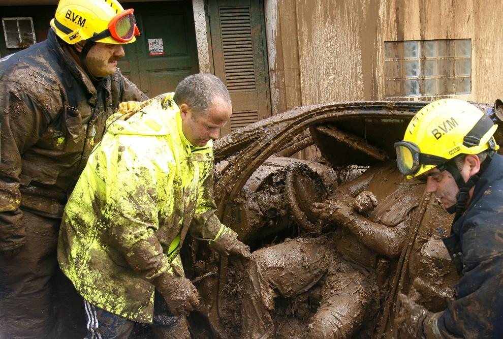 22. PORTUGALIA, |Funchal, 22 lutego 2010: Ekipa ratunkowa wydobywa ciało z zalanego błotną lawiną samochodu. AFP PHOTO/ GREGORIO CUNHA