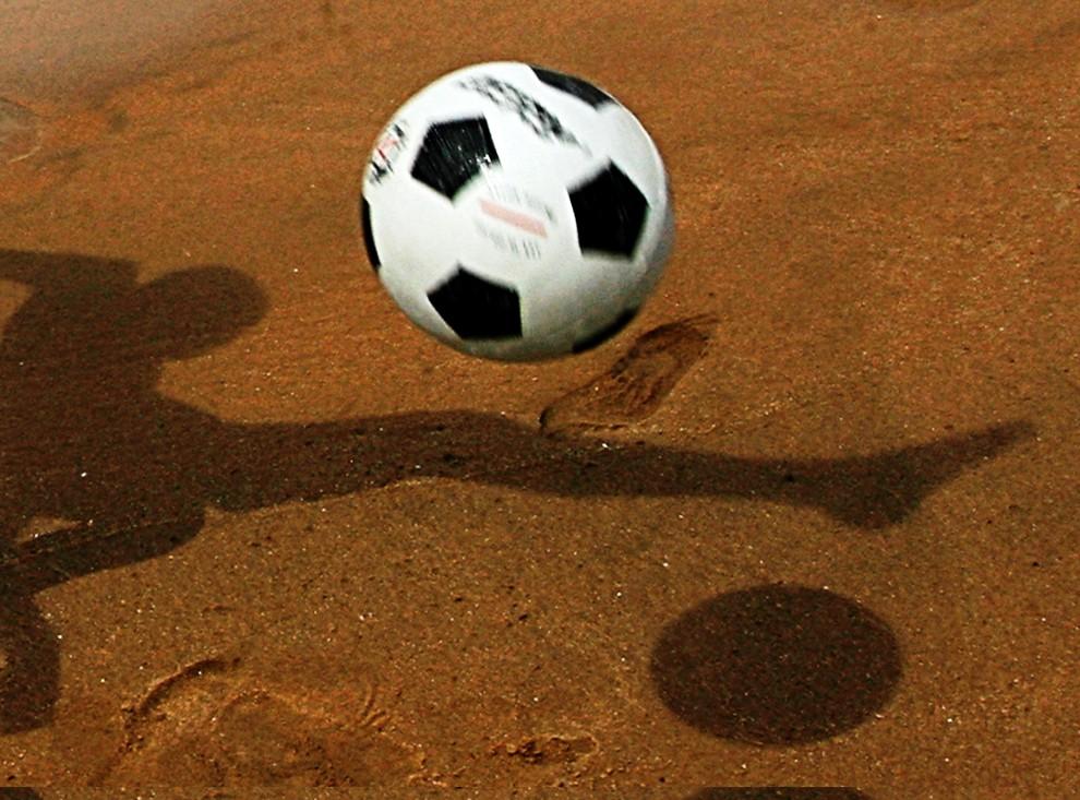23. ANGOLA, Benguela, 29 stycznia 2010: Chłopiec gra w piłkę na plaży nad Oceanem Atlantyckim. AFP PHOTO / KHALED DESOUKI