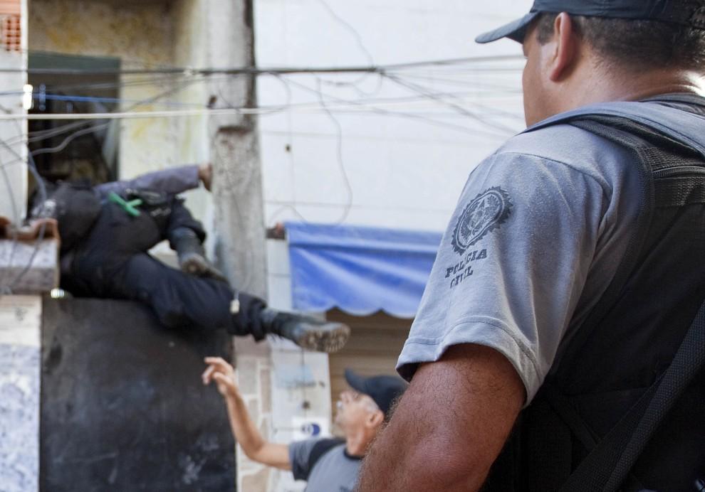 23. BRAZYLIA, Rio de Janeiro, 28 listopada 2010: Polcjant przeskakuje nad furtką podczas nalotu w faweli Morro do Alemao. AFP PHOTO / JEFFERSON BERNARDES