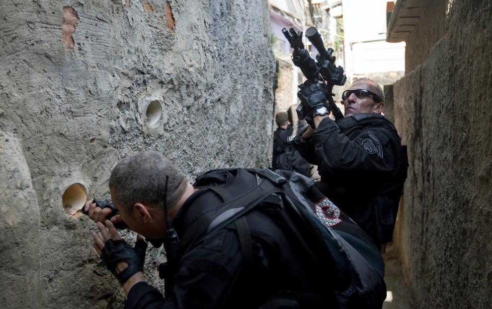24. BRAZYLIA, Rio de Janeiro, 28 listopada 2010: Policjanci z oddziałów specjalnych przeczesują fawelę  Morro do Alemao. AFP PHOTO/Jefferson BERNARDES