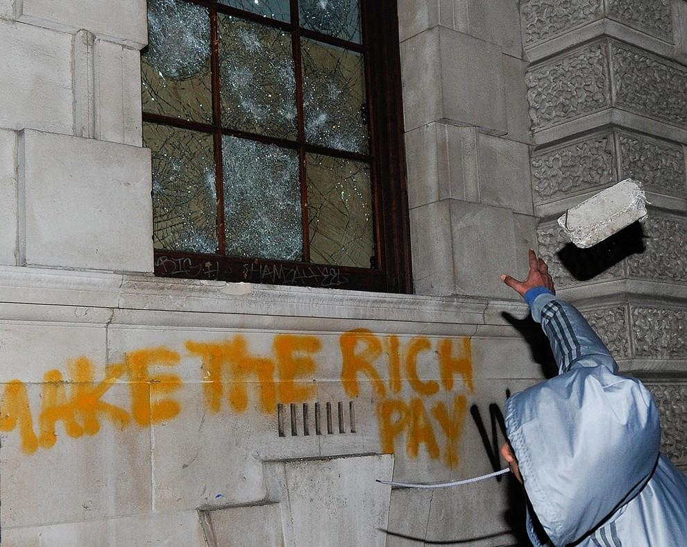 25. WIELKA BRYTANIA, Londyn, 9 grudnia 2010: Mężczyzna rzuca kamieniem w okna budynku Ministerstwa Skarbu. AFP PHOTO/CARL COURT