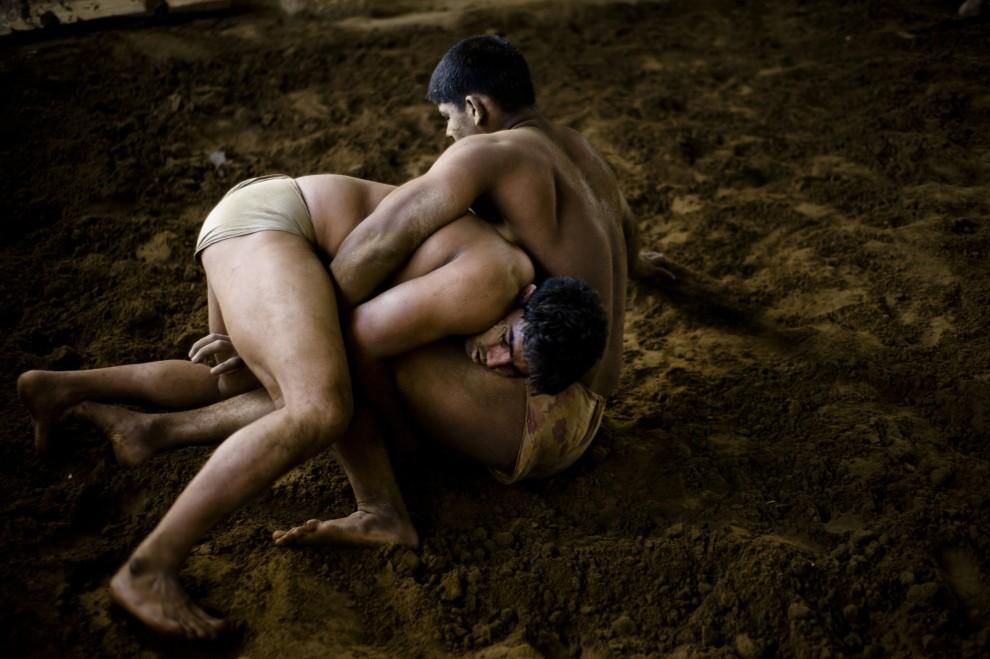 28. INDIE, New Delhi, 7 kwietnia 2010: Zapaśnicy walczą na arenie w szkole Guru Hanuman Akhara. AFP PHOTO/Manpreet ROMANA
