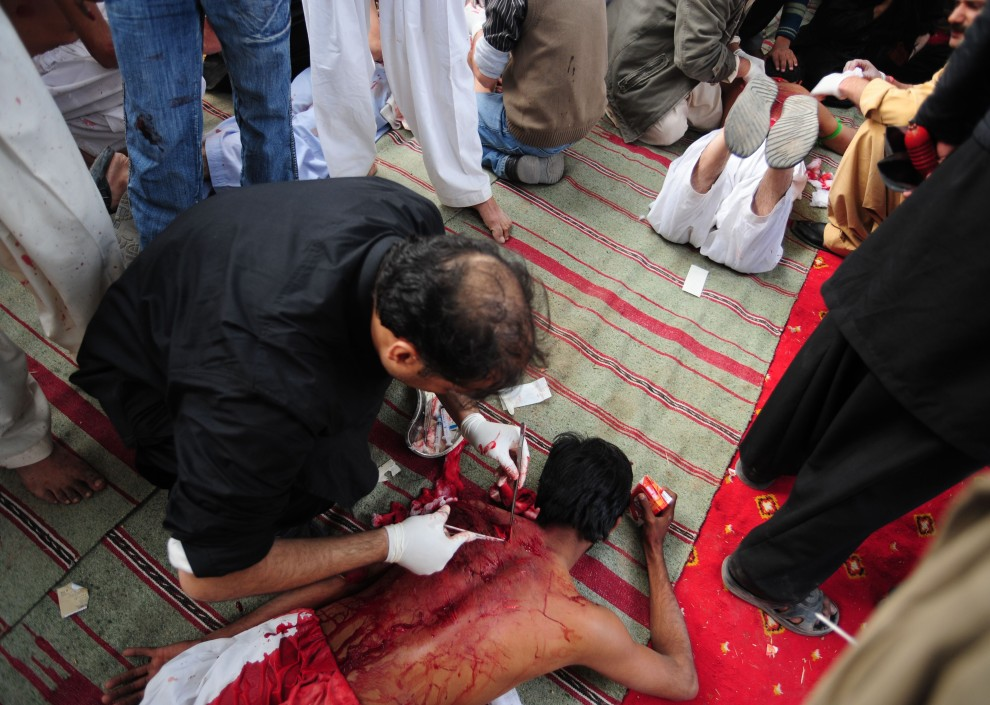 28. PAKISTAN, Islamabad, 16 grudnia 2010: Sanitariusz opatruje plecy biczownika. AFP PHOTO / Farooq NAEEM