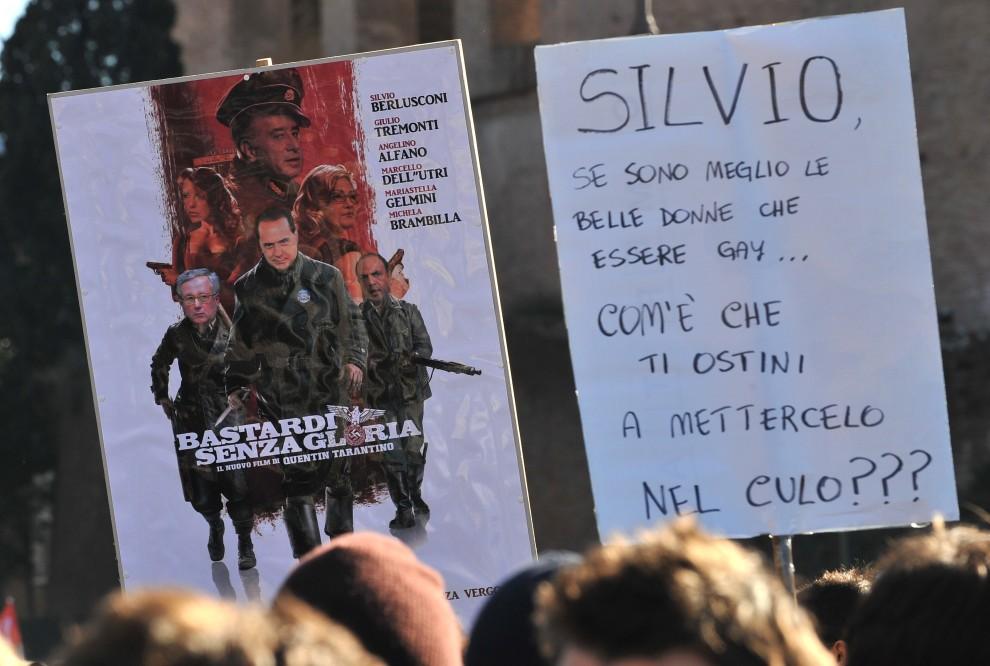 """2. WŁOCHY, Rzym, 14 grudnia 2010: Demonstrujący trzymają planszę z napisem: """"Silvio, skoro piękne kobiety są lepsze niż bycie gejem, dlaczego ciągle chcesz nas dymać w dupę?"""". AFP PHOTO / ALBERTO PIZZOLI"""