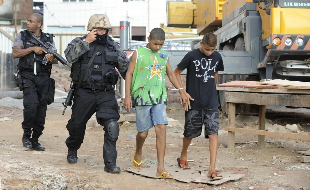 30. BRAZYLIA, Rio de Janeiro, 28 listopada 2010: Policjanci aresztują chłopców podejrzanych o handel narkotykami. AFP PHOTO / EVARISTO SA