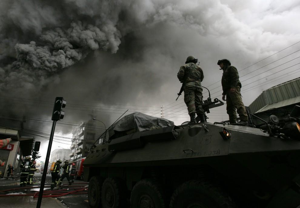 32. CHILE, Concepción, 1 marca 2010: Posterunek wojskowy w pobliżu płonącego supermarketu, który stanął w płomieniach w wyniku trzęsienia ziemi. AFP PHOTO/Claudio Santana