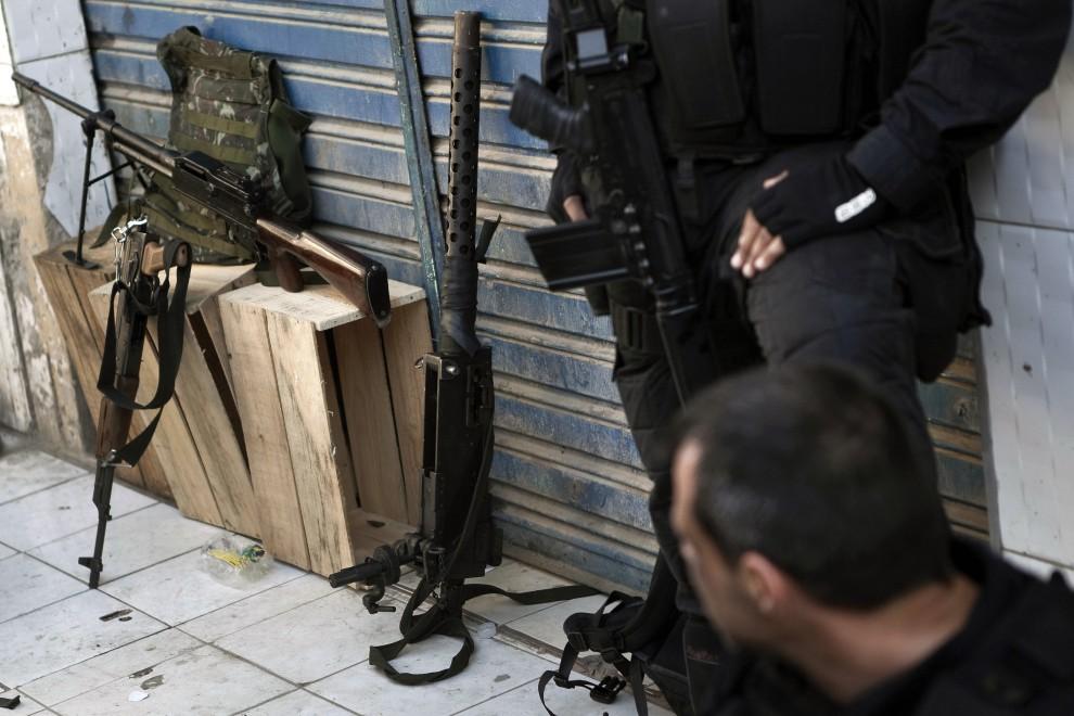 32. BRAZYLIA, Rio de Janeiro, 28 listopada 2010: Policjanci w pobliżu zarekwirowanego karabinu przeciwlotniczego. AFP PHOTO/Jefferson BERNARDES
