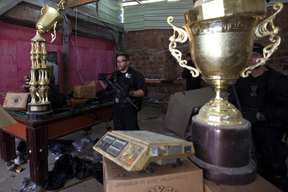 34. BRAZYLIA, Rio de Janeiro, 28 listopada 2010: Policjant przeszukuje zlokalizowane laboratorium, gdzie przetwarzano kokainę. AFP PHOTO/Jefferson BERNARDES