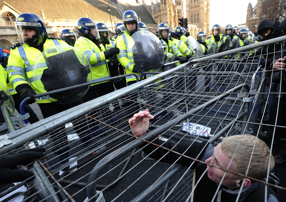 35. WIELKA BRYTANIA, Londyn, 9 grudnia 2010: Policjanci pilnują aby protestująca młodzież nie przedostała się na drugą stronę bariery wokół parlamentu. AFP PHOTO/CARL COURT