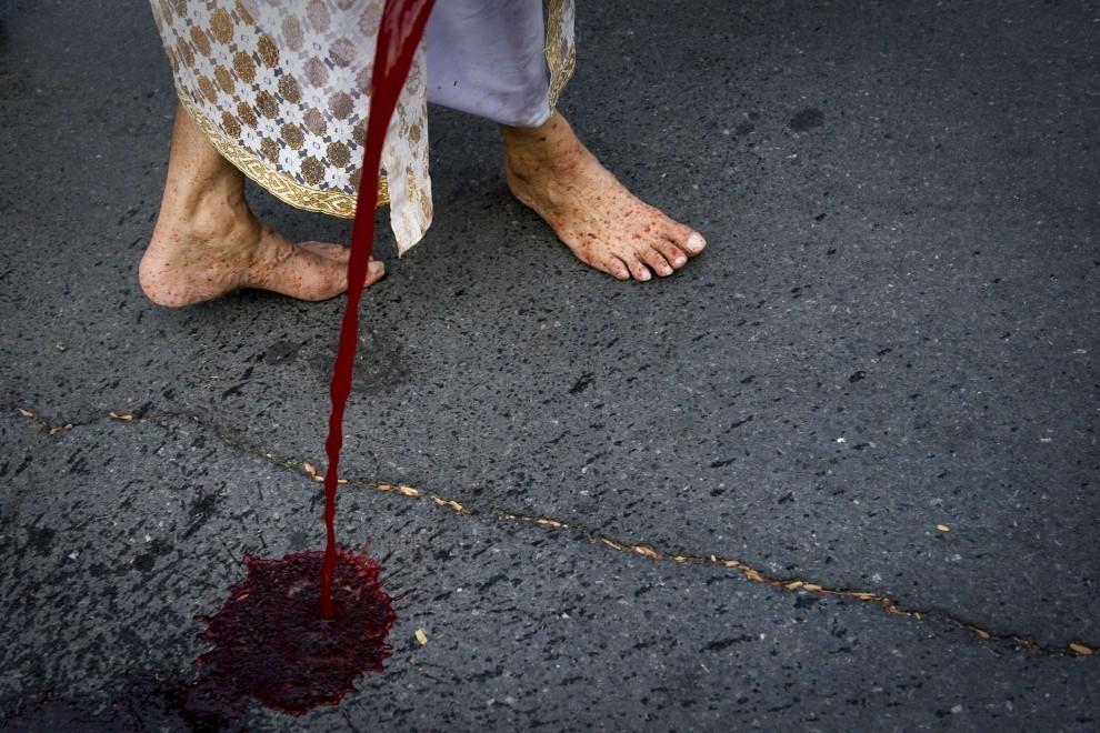 35. TAJLANDIA, Bangkok, 16 marca 2010: Zwolennik byłego premiera, Thaksina Shinawatra, rozlewa ludzką krew przed budynkiem parlamentu w Bangkoku. AFP PHOTO/   Nicolas ASFOURI