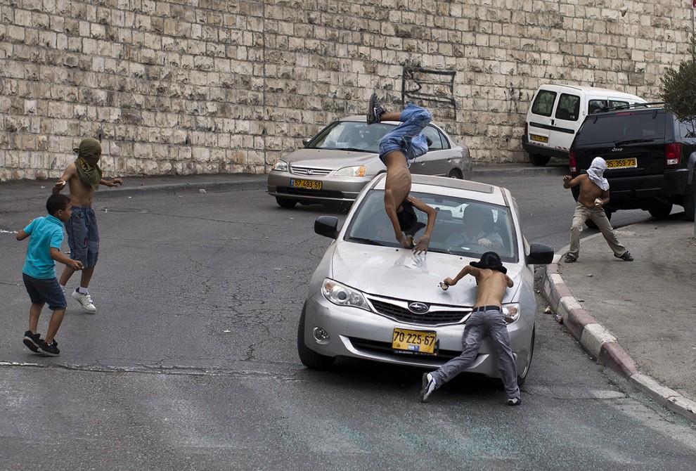 37. IZRAEL, Jerozolima, 8 października 2010: Izraelski samochód wjeżdża w grupę palestyńskich chłopców obrzucających go kamieniami. AFP PHOTO/ILIA YEFIMOVICH