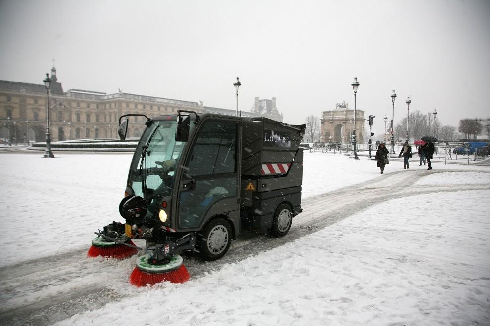 3. FRANCJA, Paryż, 19 grudnia 2010: Pojazd służb porządkowych Luwru zgarnia śnieg sprzed muzeum. (Foto: Marc Piasecki/Getty Images)