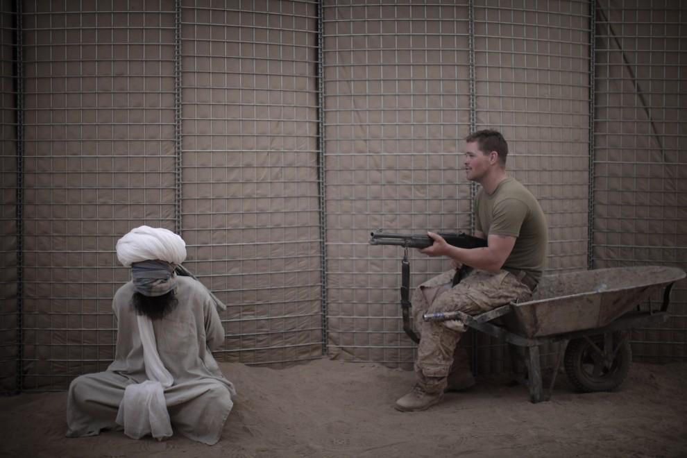 40. AFGANISTAN, Mardża, 7 kwietnia 2010: Amerykański żołnierz piechoty morskiej pilnuje zatrzymanego Afgańczyka. AFP PHOTO/Mauricio LIMA