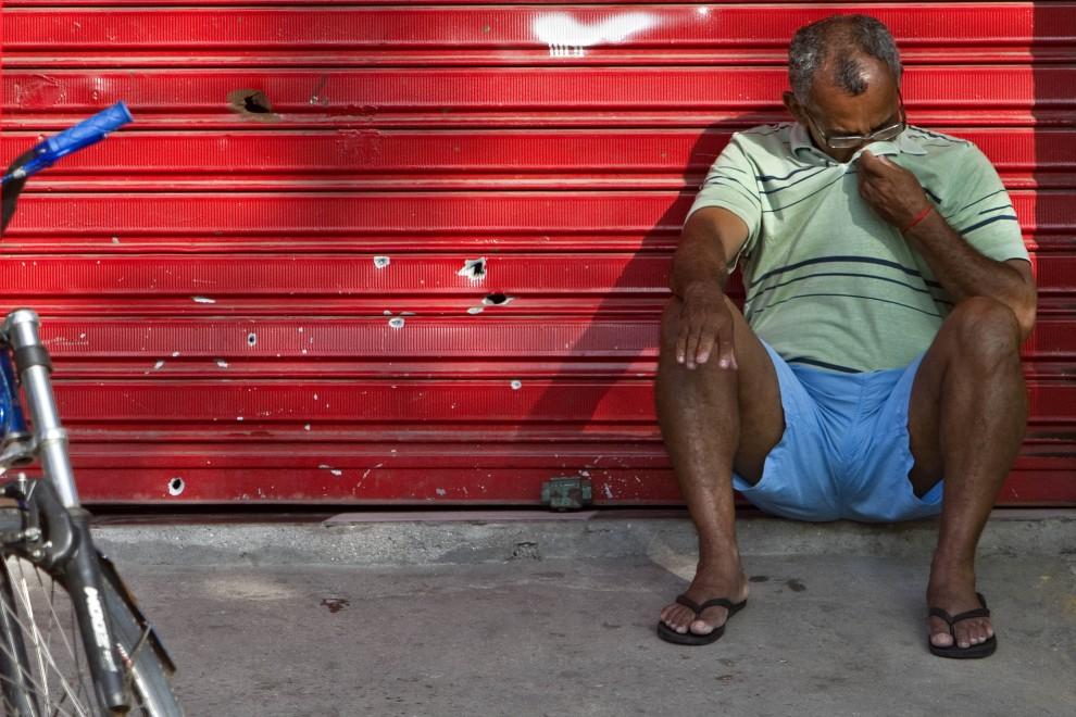 41. BRAZYLIA, Rio de Janeiro, 27 listopada 2010: Mężczyzna siedzi na ulicy opierając się o metalową kurtynę. AFP PHOTO/ Jefferson BERNARDES