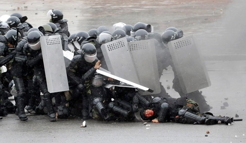 43. KIRGISTAN, Biszkek, 7 kwietnia 2010: Policjanci starają się chronić rannego kolegę podczas starć z opozycjonistami. AFP PHOTO / VYACHESLAV OSELEDKO