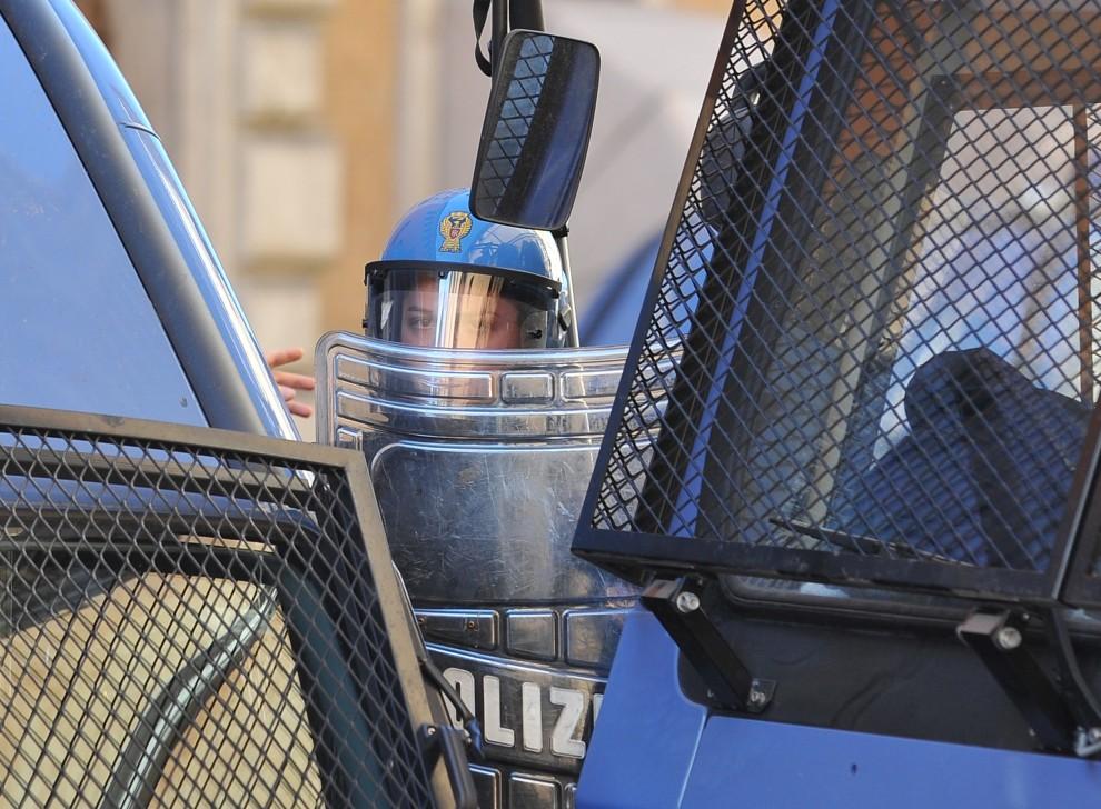 4. WŁOCHY, Rzym, 14 grudnia 2010: Policjantka stoi za barykadą z samochodów policyjnych. AFP PHOTO / ALBERTO PIZZOLI