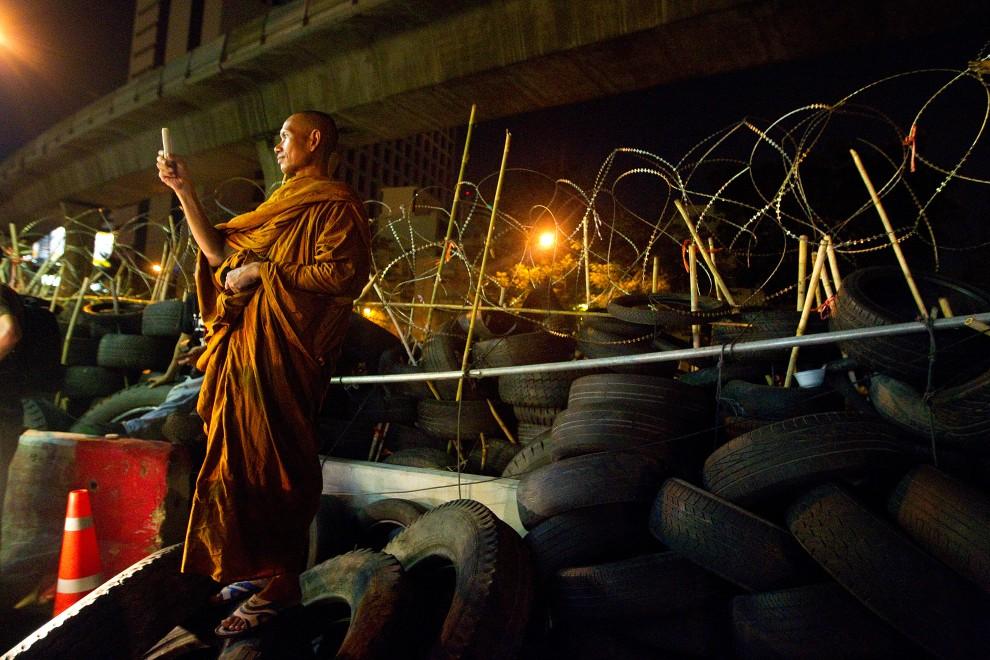 """51. TAJLANDIA, Bangkok, 4 maja 2010: Buddyjski mnich robi zdjęcie telefonem komórkowym podczas protestów """"czerwonych koszul"""". (Foto: Paula Bronstein/Getty Images)"""