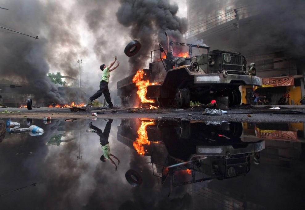 52. TAJLANDIA, Bangkok, 16 maja 2010: Mężczyzna rzuca oponę w kierunku płonącej wojskowej ciężarówki. (Foto: Athit Perawongmetha/Getty Images)
