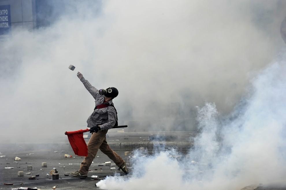 53. 1GRECJA, Ateny, 5 maja 2010: Protestujący ciska kamieniem w kordon policji rozstawiony wokół budynku parlamentu. AFP PHOTO / ARIS MESSINIS