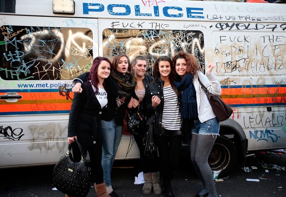 53. WIELKA BRYTANIA, 24 listopada 2010: Studentki pozują przy zniszczonym, podczas zamieszek radiowozie. (Foto: Matthew Lloyd/Getty Images)