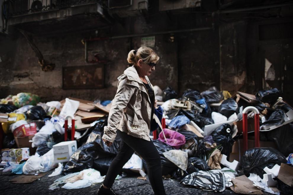 57. WŁOCHY, Neapol, 22 listopada 2010: Kobieta przechodzi obok sterty śmieci, jakie zalegają na ulicach Neapolu w wyniku strajków służb porządkowych. AFP PHOTO / FILES / ROBERTO SALOMONE