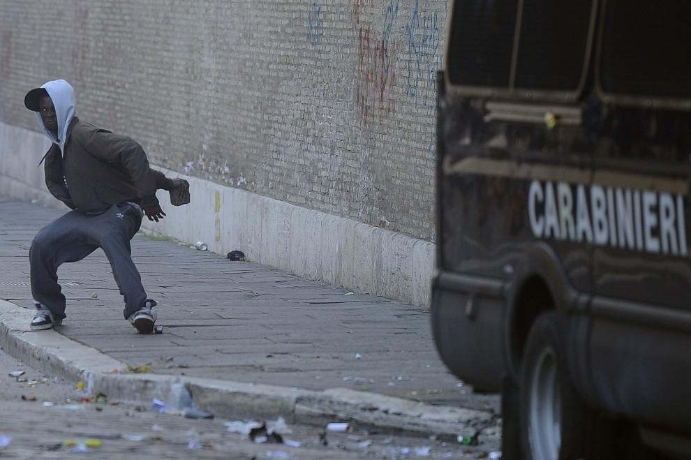 63. WŁOCHY, Rzym, 14 grudnia 2010: Mężczyzna ciska kamieniem w kierunku policjantów. AFP PHOTO / FILIPPO MONTEFORTE