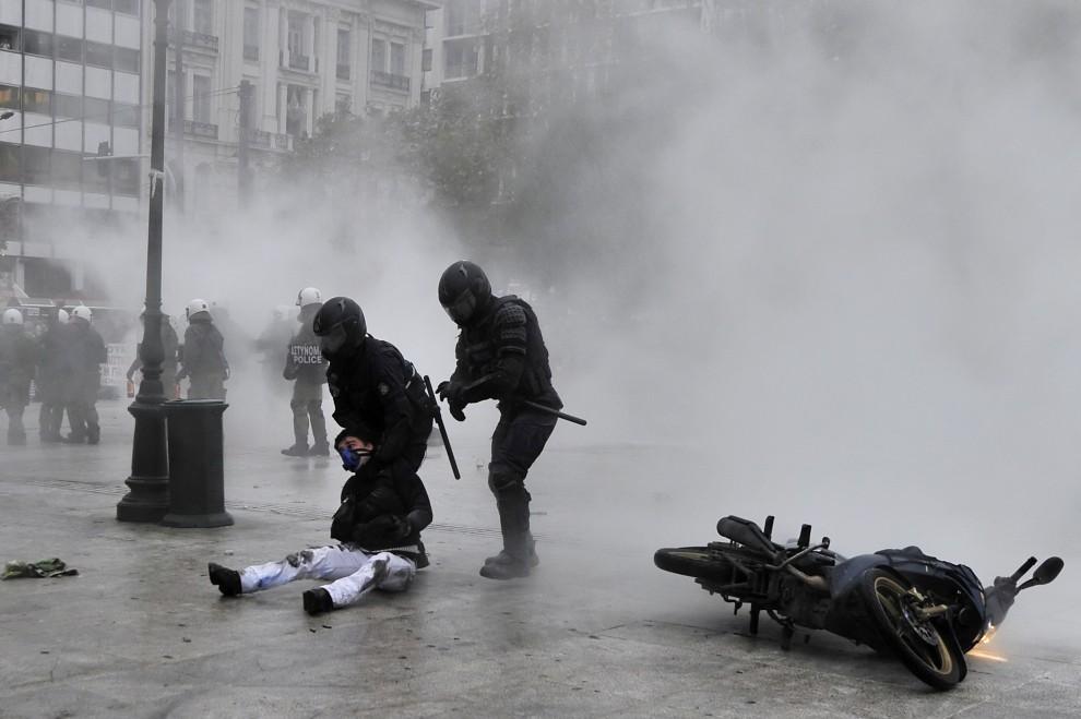 64. GRECJA, Ateny, 15 grudnia 2010: Policjanci aresztują demonstranta podczas zamieszek w Atenach. AFP PHOTO / Aris Messinis