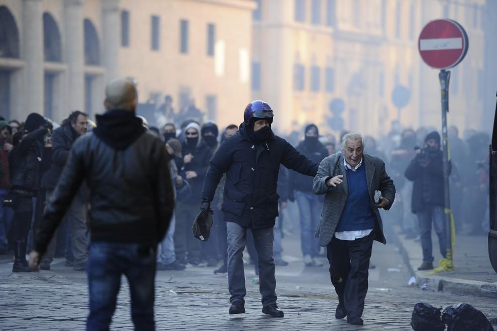 6. WŁOCHY, Rzym, 14 grudnia 2010: Policjant odprowadza przechodnia, który przypadkowo znalazł się między protestującymi a kordonem policji. AFP PHOTO / FILIPPO MONTEFORTE