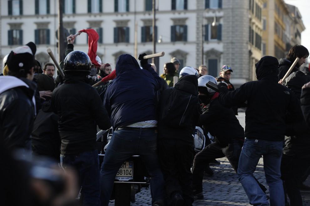 8. WŁOCHY, Rzym, 14 grudnia 2010: Protestujący atakują policjanta na motocyklu. AFP PHOTO / FILIPPO MONTEFORTE
