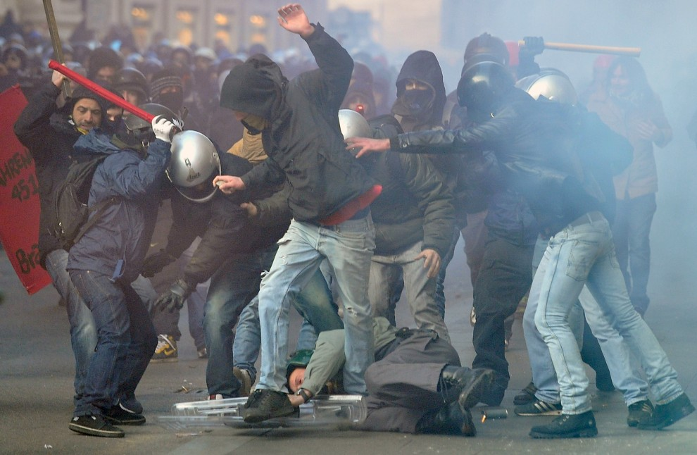9. WŁOCHY, Rzym, 14 grudnia 2010: Leżący policjant atakowany przez demonstrantów. AFP PHOTO / ALBERTO PIZZOLI