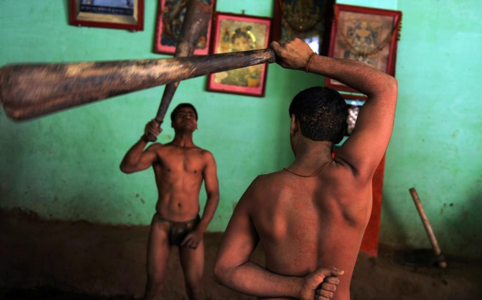 9. INDIE, Allahabad, 19 kwietniu 2010: Zapaśnicy trenują z maczugami w szkole w Allahabadzie. AFP PHOTO/Diptendu DUTTA