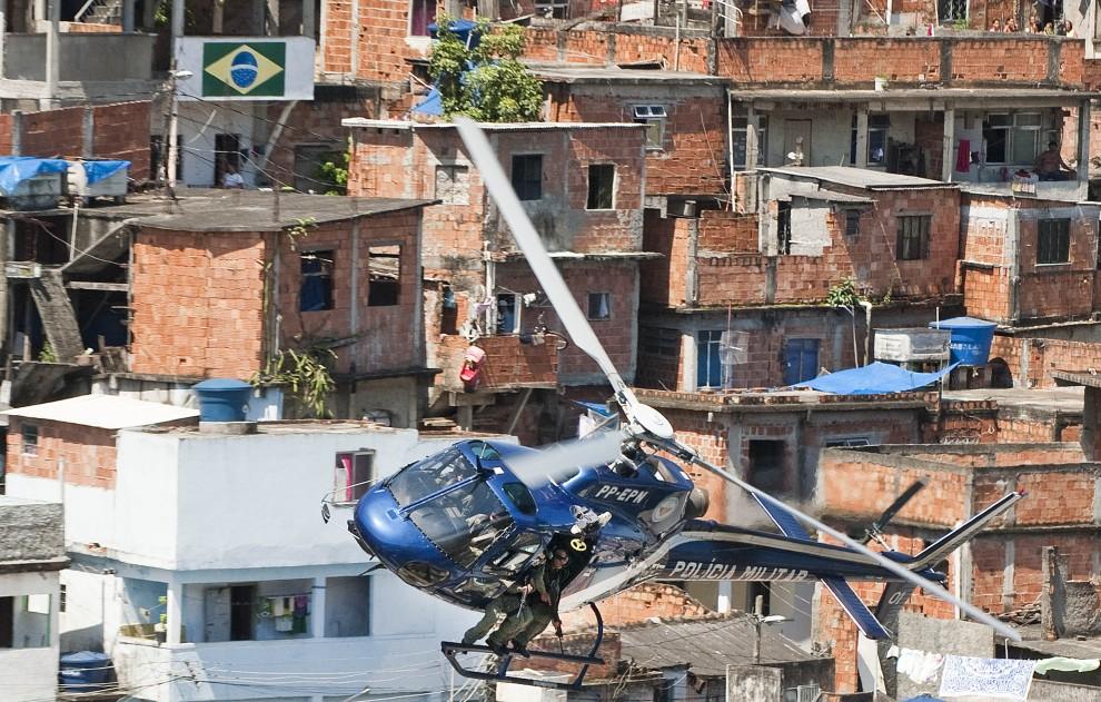9. BRAZYLIA, Rio de Janeiro, 28 listopada 2010: Wojskowy helikopter przelatuje nad fawelą Morro do Alemao. AFP PHOTO/Antonio Scorza