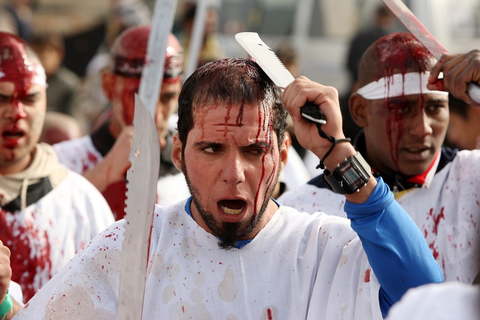 9. IRAK, Bagdad, 17 grudnia 2010: Mężczyźni z krwawiącymi głowami uczestniczą w rytualnej procesji. AFPPHOTO/AHMAD AL-RUBAYE