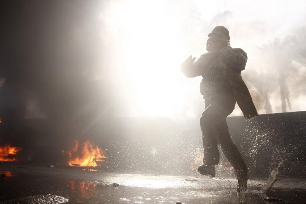 10. EGIPT, Suez, 28 stycznia 2011: Protestujący ucieka przed napierającymi oddziałami policji. AFP PHOTO/STR